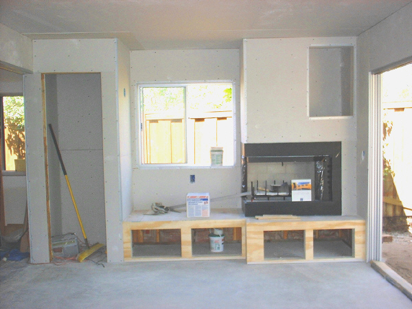 Room addition, 7-18: This photo shows the wall with the fireplace, elevated hearth, and closet, now drywalled. Note the cabinet openings under the hearth and beside the chimney.