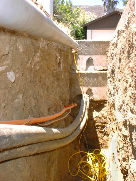 Room addition, 8-05: This photo from inside the electrical trench shows the new conduit with pull-rope, existing service mains, and gas line (in orange).